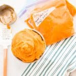 Horizontal image: gray bowl filled with sweet potato puree next to three bags filled with sweet potato puree in a green and white kitchen.
