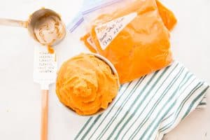 Sweet potato puree in a gray bowl next to a green and white striped kitchen towel bags filled with sweet potato puree are marked with a date