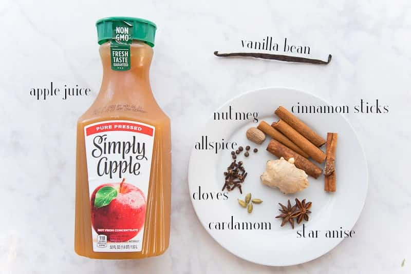 Ingredients needed to make spiced apple cider apple juice, vanilla bean, cinnamon sticks, ginger, star anise, cardamom, cloves, allspice, and nutmeg on a white plate.