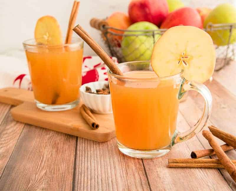 Horizontal image of two clear glass mugs filled with slow cooker spiced apple cider garnish with cinnamon sticks on a wooden surface.