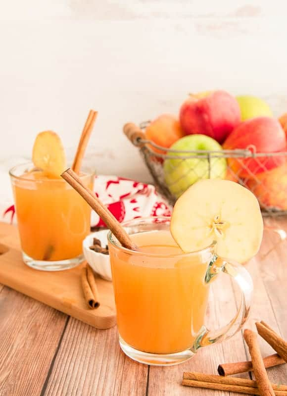 Portrait image 2 glass mugs filled with slow cooker spiced apple cider on wooden background in front of a basket of multicolored apples.