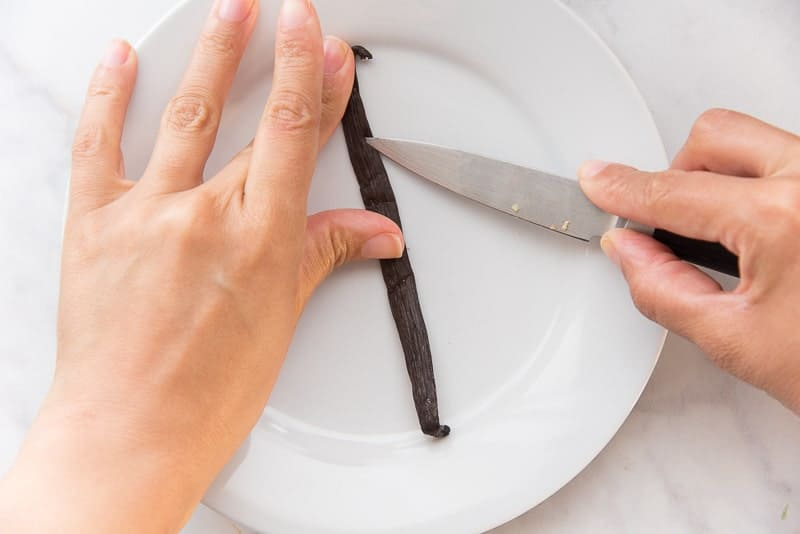 Two hands use a paring knife to split a vanilla bean down the middle on a white plate.