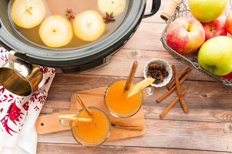 Overhead image of two clear glass mugs filled with slow cooker spiced apple cider garnished with cinnamon sticks. Top left of the image: a slow cooker has the rest of the cider inside of it with apple slices and star anise floating on the surface.