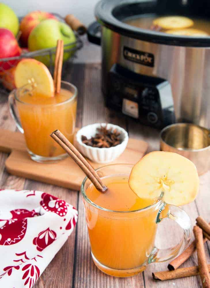 Orchard image of to clear glass mugs filled with slow cooker spiced apple cider garnish with cinnamon sticks background of image has a slow cooker and a basket of multicolored apples.