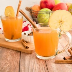 Horizontal image of two glass mugs filled with spiced apple cider garnished with cinnamon sticks and sliced apples a basket of apples is in the background.