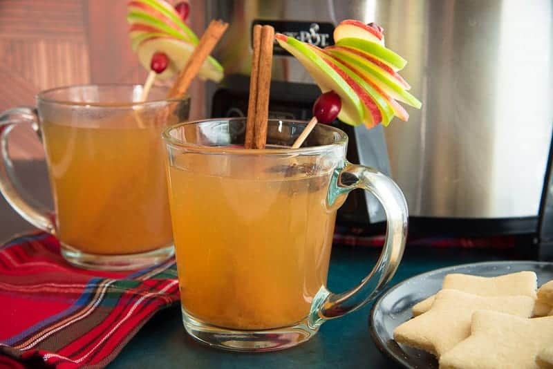 Horizontal image of two glass mugs filled with slow cooker wassail in front of a slow cooker. To the right is a plate black plate with sugar cookies on top.