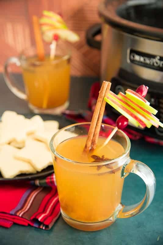 Portrait image of a clear glass mug filled with slow cooker Wassail garnished with apple pinwheel, cinnamon sticks, and star anise lights background a black plate with sugar cookies on top.