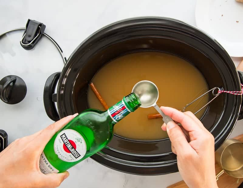 Dry vermouth is poured into a measuring spoon over a slow cooker filled with apple cider and wine.