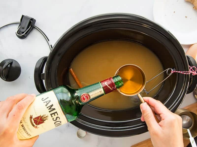 Irish whiskey is poured from a green bottle into a measuring cup over the slow cooker.