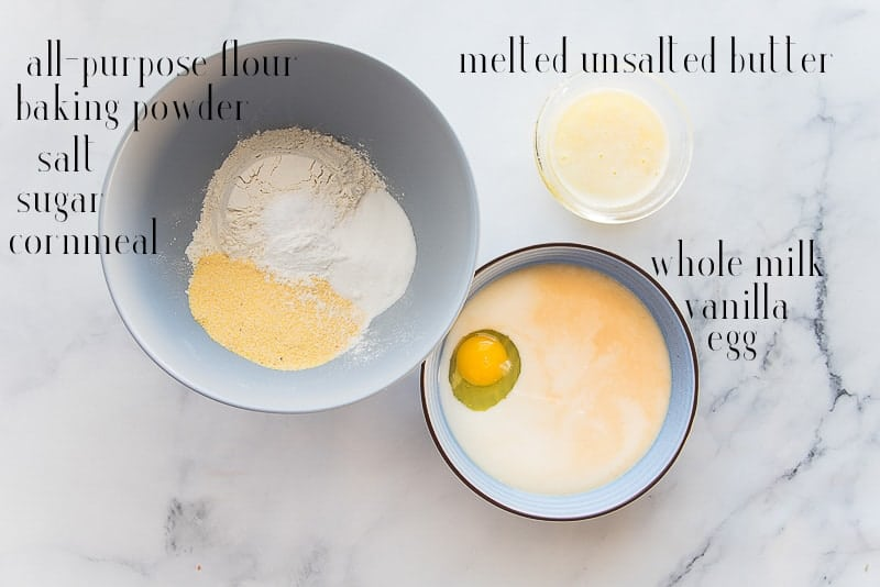 Ingredients needed to make cornbread: flour, baking powder, salt, sugar, carnmeal, unsalted butter, whole milk, vanilla, and an egg.