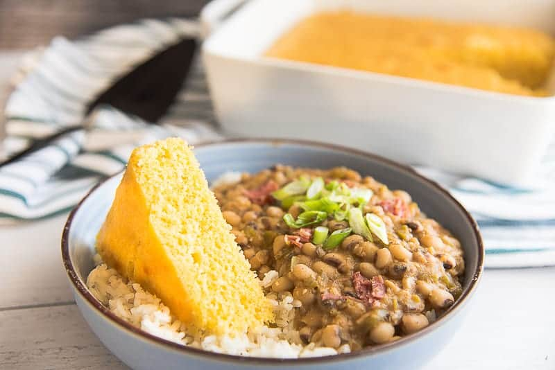 A horizontal image of a blue bowl with a brown rim, filled with white rice and black eyed peas, topped with a wedge of yellow cornbread.