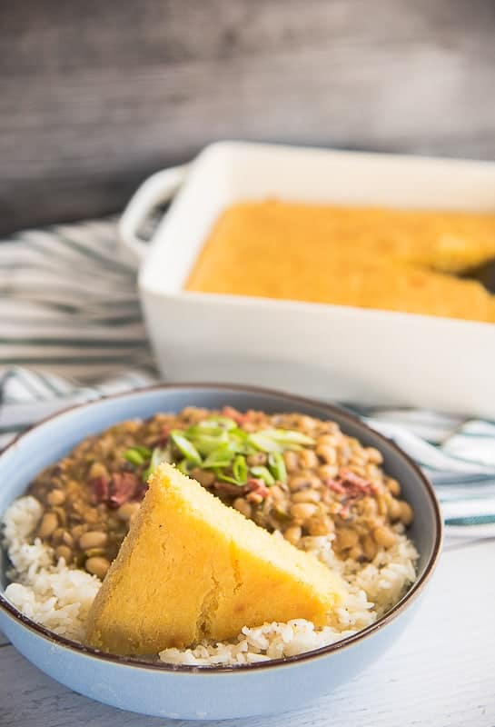 Portrait image of a blue bowl on white rice topped with a slice of yellow cornbread