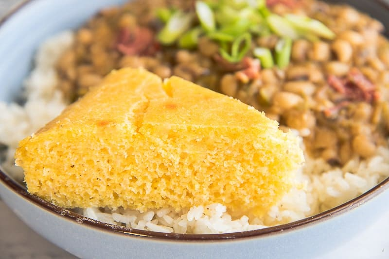 A close up image of a slice of cornbread on a pile of white rice in a light blue bowl