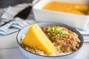 horizontal image of a blue bowl with a brown rim filled with rice, pease and a triangle slice of yellow cornbread