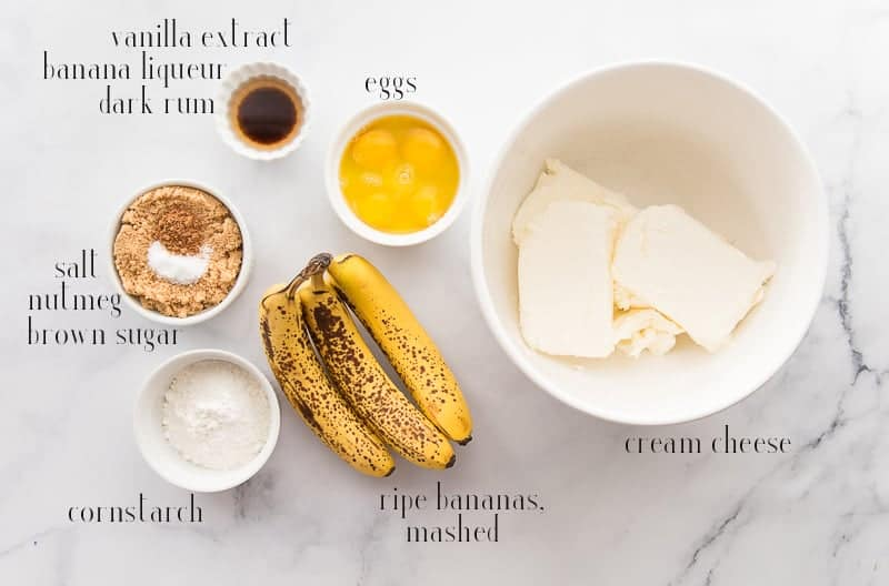 The ingredients to make Banana Cheesecake: cream cheese, bananas, eggs, cornstarch, brown sugar. salt, nutmeg, vanilla, rum, and banana liqueur