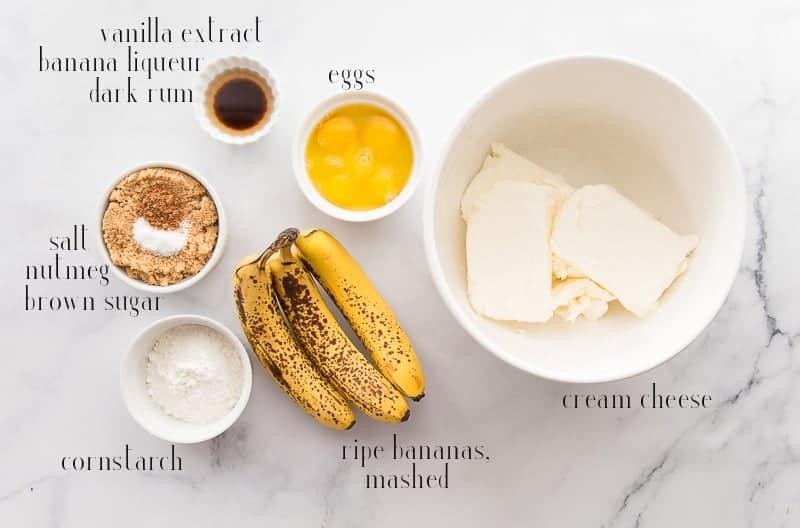 The ingredients to make Banana Cheesecake: cream cheese, bananas, eggs, cornstarch, brown sugar. salt, nutmeg, vanilla, rum, and banana liqueur