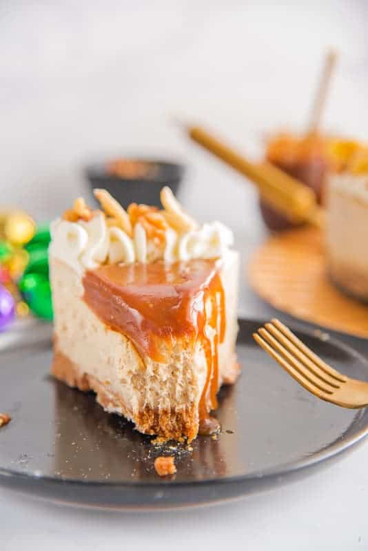 A slice of Bananas Foster Cheesecake on a black plate with gold fork.