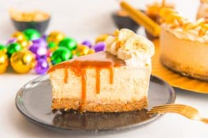 A slice of Bananas Foster Cheesecake drizzled with rum caramel on a black plate in front of gold, green, and purple Mardi Gras beads.
