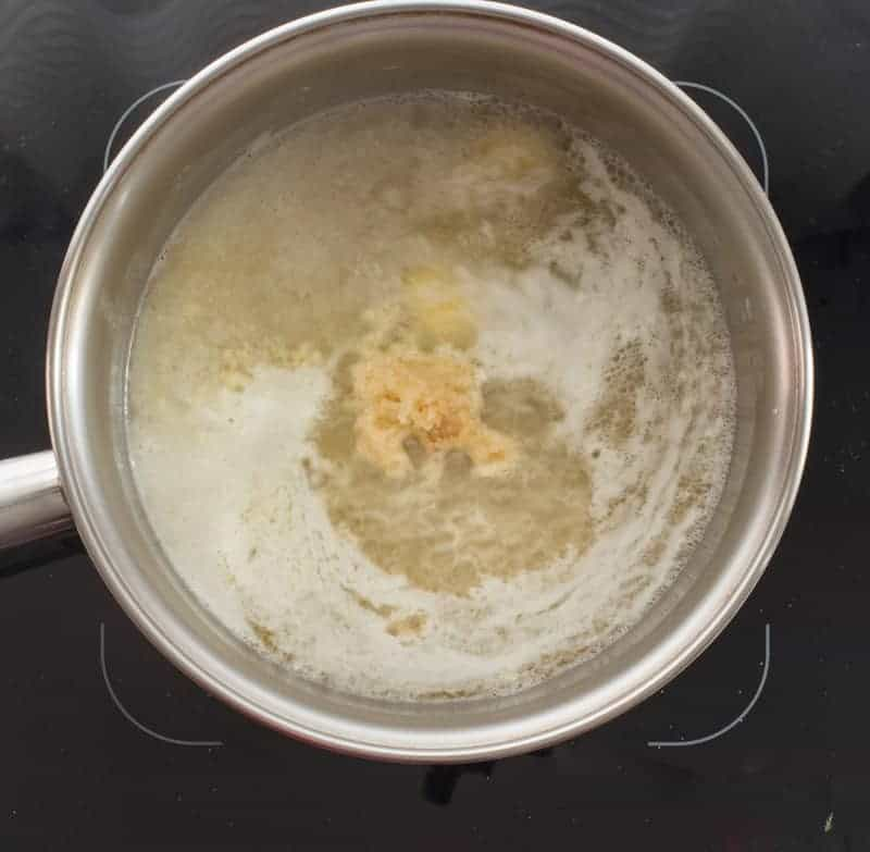 Butter, lemon juice, and garlic are simmered in a metal pot