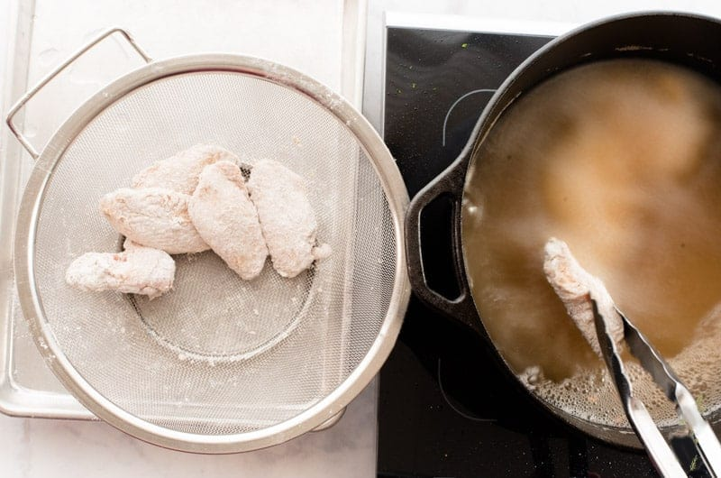 Flour coated wings before frying in a mesh colander next to a pot of frying oil.