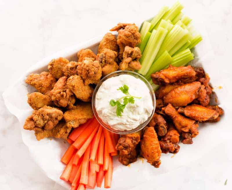 A horizontal image of a Buffalo Wing Platter with blue cheese, celery and carrots