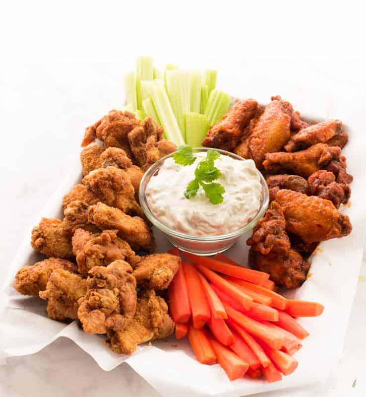 A Buffalo Wing Platter with two flavors of wings on a paper-lined dish. A bowl of blue cheese in center