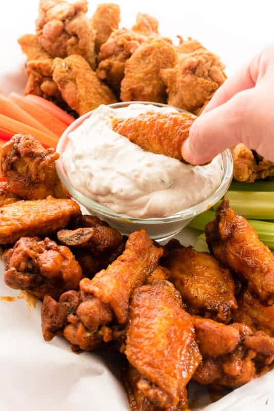 A hand dipping a buffalo wing in blue cheese dip. The platter of wings, carrots, and celery in background