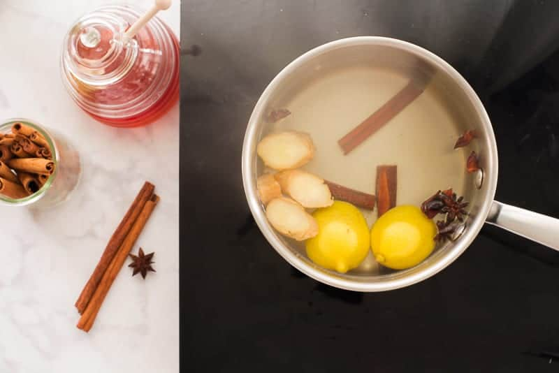 Cinnamon sticks, star anise, ginger, and lemon rinds are simmering in a silver pot on a black stove.