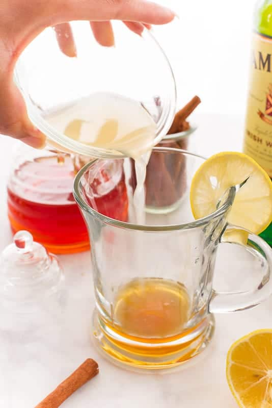 A hand pours lemon juice from a clear glass bowl into a glass mug with honey in it.