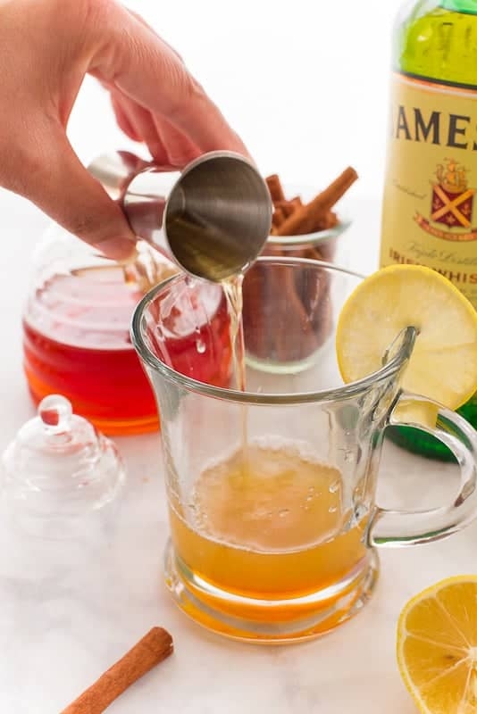 A hand pours whiskey from a silver jigger into a honey and lemon juice-filled clear glass mug