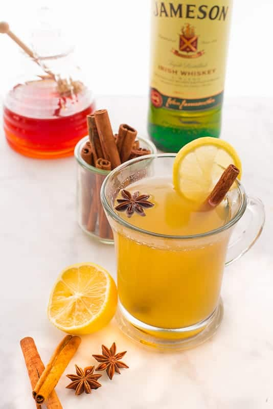 Portrait image of a clear mug of Classic Hot Toddy surrounded by lemon half, cinnamon sticks, star anise, cinnamon stick in glass jar in the background, honey pot and a bottle of Irish whiskey.