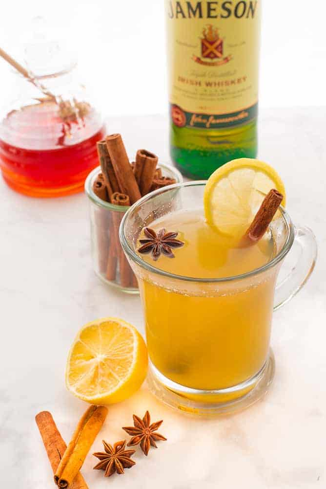Lead image: a clear mug of Classic Hot Toddy garnished with a cinnamon stick, star anise, and a lemon slice. Two cinnamon sticks, star anise, and half a lemon to the left of mug.