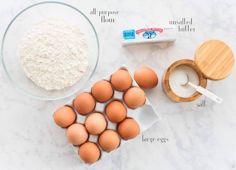 Ingredients to make pate a choux: all-purpose flour, unsalted butter, salt, and large eggs on a white surface.