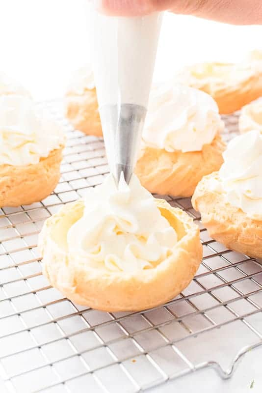 A hand pipes white whipped cream into a pate a choux shell