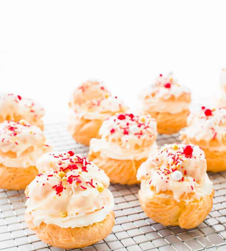 Cream Puffs filled with whipped cream and topped with white chocolate ganache and Valentine's sprinkles sit on a silver cooking rack