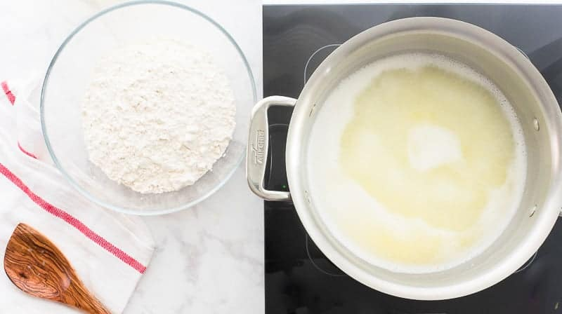 The water, butter, and salt are rapidly boiled in a silver a pot. A bowlful of white flour sits ready to be added with a wooden spoon