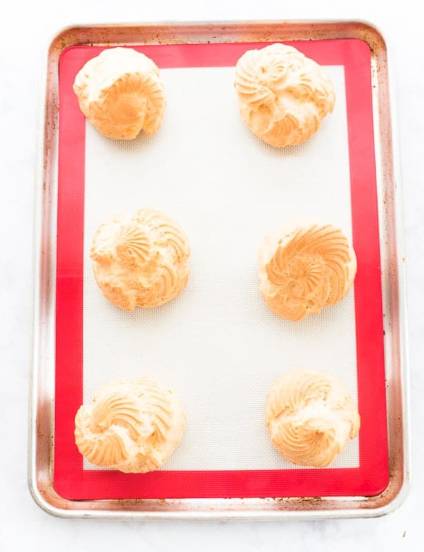 Six baked pate a choux shells on a red and white silicone baking mat