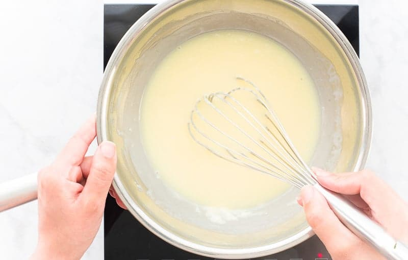 A hand uses a whisk to finish combining the melted white chocolate and heavy cream to make white chocolate ganache