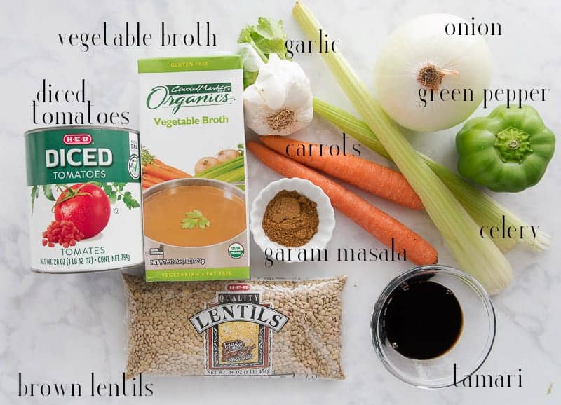 The ingredients needed for Vegan Lentil Stew: canned tomatoes, vegetable broth, onion, garlic, green pepper, carrots, celery, tamari, garam masala, lentils on a white surface