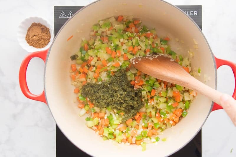 Sautéing carrots, celery, onions, garlic, and sofrito stirred with a wooden spoon in a red pot.
