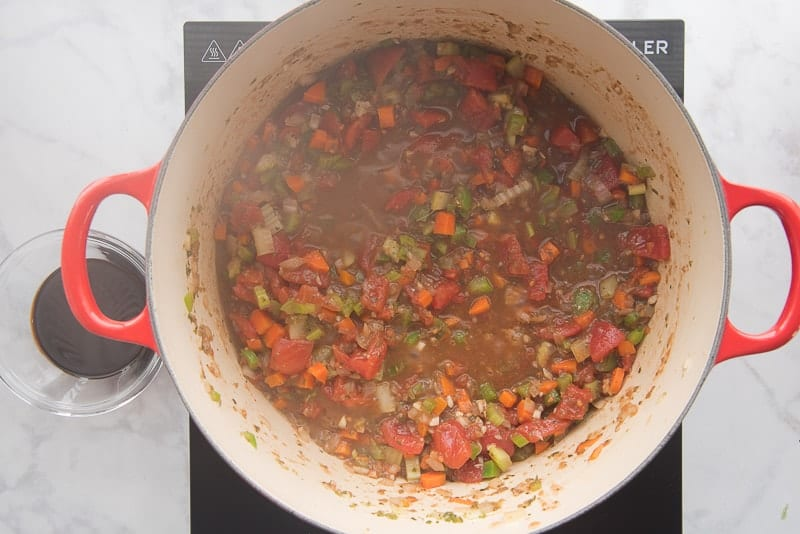 Tomatoes and mirepoix are simmered in a red dutch oven.