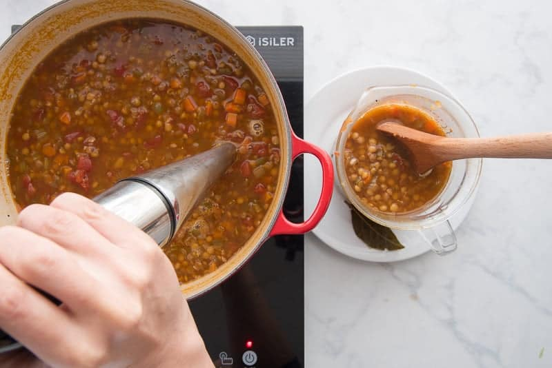 An immersion blenders blending lentils in a red pot. A glass measuring cup filled with whole lentils a wooden spoon sticks out of the measuring cup.