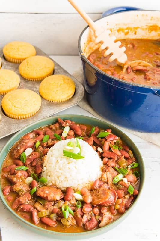 Portrait image of a green bowl of Creole red beans and rice in foreground. A pan of corn muffins in back left a blue pot of beans in top right.
