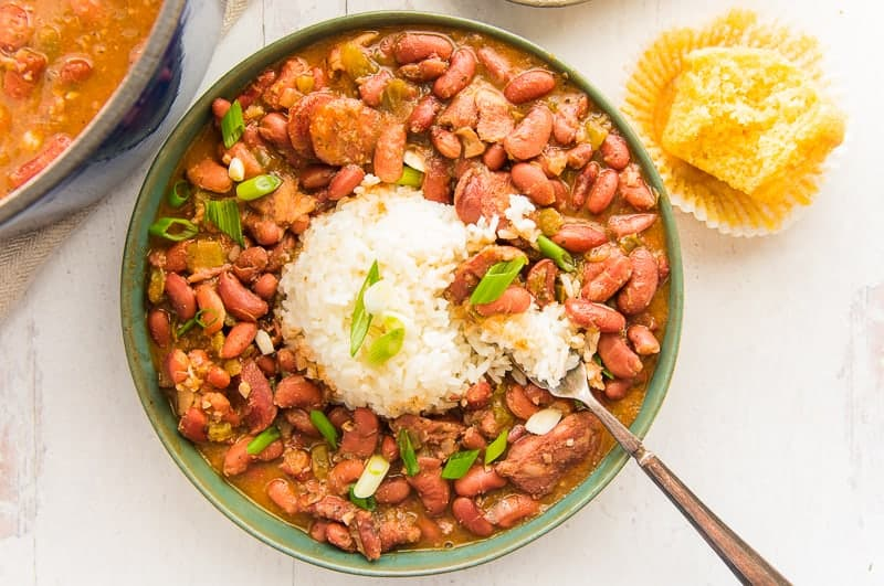 Overhead image of a green bowl of creole red beans and rice with a silver fork. Garnished with green onion. An unwrapped cornbread muffin with a bite removed on top right.