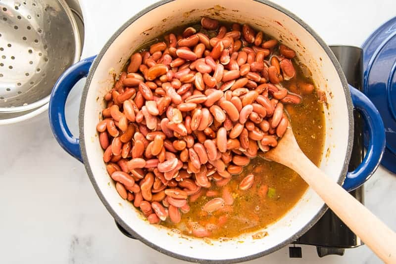 The soaked legumes are stirred into the sauce in a blue pot with a wooden spoon.