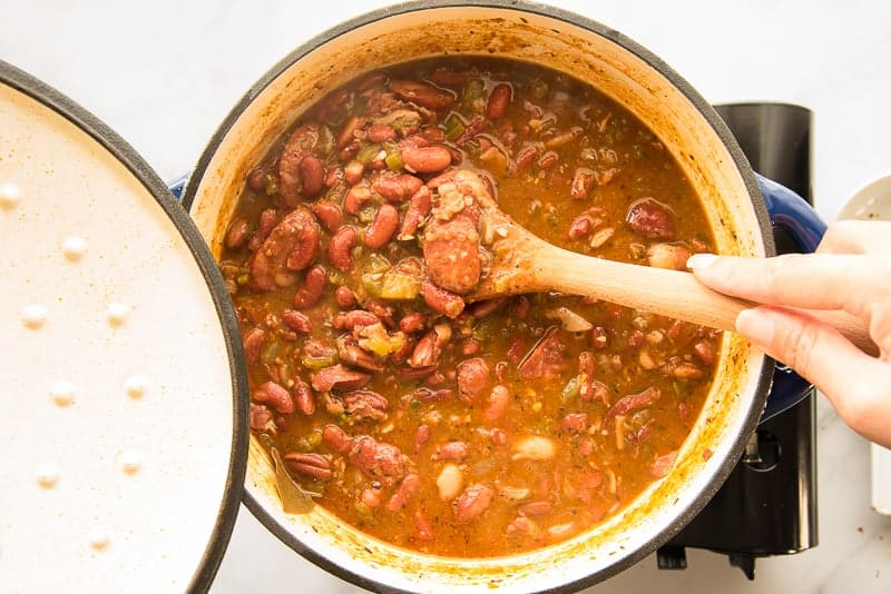 A hand uses a wooden spoon to stir the finished beans in a blue pot.