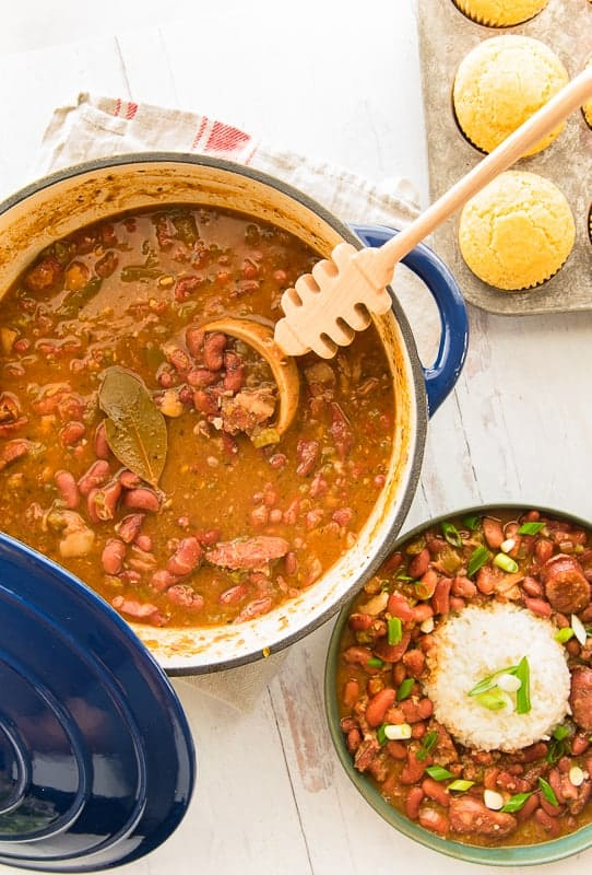Overhead portrait image of a green bowl of Creole red beans and rice next to a blue pot of beans with wooden spoon stuck in it.