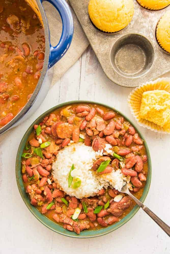 Lead image: green bowl of beans and rice garnished with green onion. A bitten cornbread muffin is unwrapped in top right corner of image.