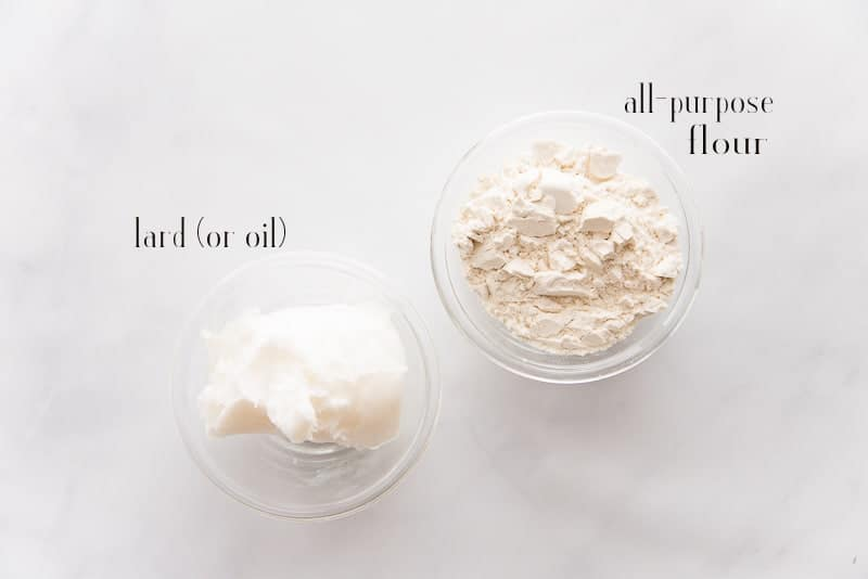 Ingredients for the roux on a marble surface: lard and all-purpose flour
