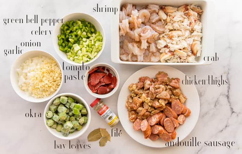 The ingredients for gumbo on a marble surface: green bell pepper, celery, onion, garlic, tomato paste, okra, bay leaves. filé, sausage, chicken, crab, and shrimp